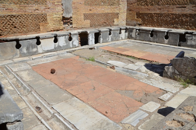 The latrines near the Forum Baths at Ostia Antica (Italy). The stone seating is still preserved around the walls, and there is a small basin next to the pillar which separates the two doorways into the room.