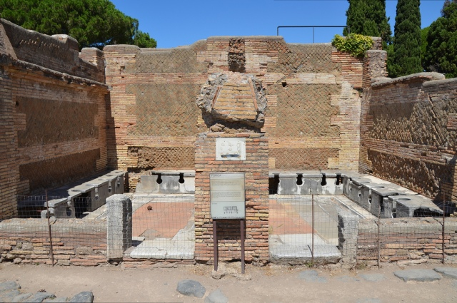 The latrines at near the Forum Baths at Ostia Antica (Italy). The stone seating is still preserved around the walls, and there is a small basin next to the pillar which separates the two doorways into the room.