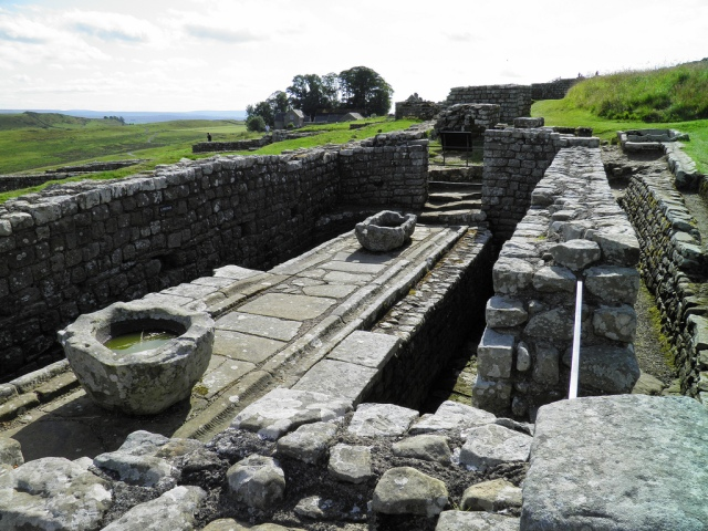 The Latrines at Housesteads Fort in Great Britain. There were wooden seats along the sides, set over a deep channel. A smaller channel in the centre of the building was used for washing sponges.