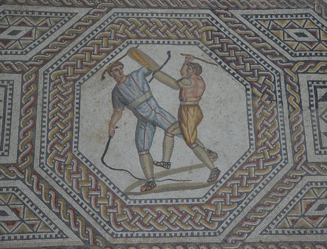 Two combatants attacking one another with cudgels and a whip, the gladiator mosaic at the Roman villa in Nennig, Germany © Carole Raddato