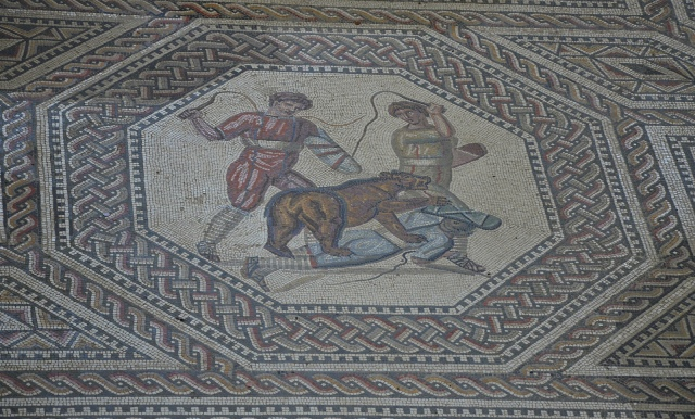 Panel depicting a two rogues trying to drive the animal off by lashes from their whips, the gladiator mosaic at the Roman villa in Nennig, Germany © Carole Raddato