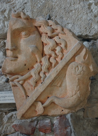 Fragment of a tombstone with depictions of Medusa and a dolphin, 1st - 2nd century AD, on display in the Temple of Augustus
