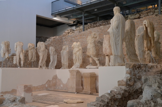 The remains of the Augusteum and fifteen marble sculptures exhibited on a platform, Archaeological museum Narona © Carole Raddato