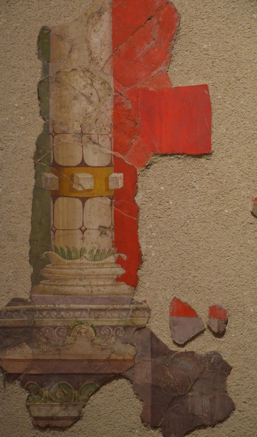 Fresco in Second Pompeian style with decoration of architectural type on a red background, discovered at the Villa de Roquelaure, dating to around 20 BC Empire of colour. From Pompeii to Southern Gaul, Musée Saint-Raymond Toulouse © Carole Raddato