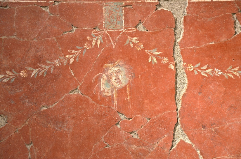 Fresco fragment with mask and Tympanum (tambourine) on red background, from Narbonne, 2nd century AD Empire of colour. From Pompeii to Southern Gaul, Musée Saint-Raymond Toulouse On loan from Narbonne Archaeological Museum Carole Raddato CC BY-SA
