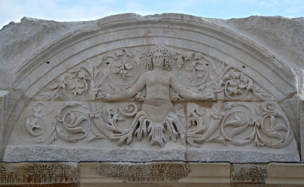 The tympanum of the Temple of Hadrian, a semi-circular relief over the entrance door depicting a female figure among acanthus leaves and scrolls, Ephesus, Turkey Carole Raddato CC BY-SA