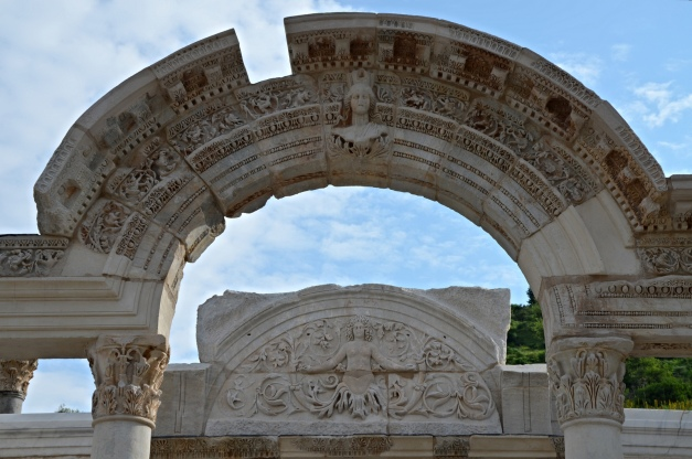 The archivolt with inscription decorated with the crowning bust of the goddess Tyche, and behind the cella's tympanon of the Temple of Hadrian on Curetes Street, built before 138 AD by the asiarch P. Vedius Antoninus Sabinus, Ephesus, Turkey Carole Raddato CC BY-SA