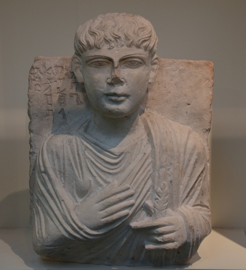 Limestone bust including head and upper torso of a clean-shaven man wearing a toga and holding a feather (quill pen?), ca. 150-200 AD, from Palmyra, Syria, British Museum Carole Raddato CC BY-SA