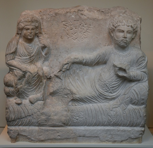 Limestone funerary relief carved with bearded man reclining on richly covered couch with wife seated beside and Palmyrene inscription 200-273 AD, from Palmyra, Syria, British Museum Carole Raddato CC BY-SA