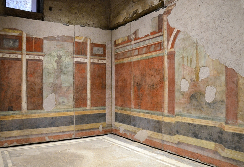 The triclinium (dining room) decorated with an elaborate design of illusionistic architecture featuring a large picture of a sacred and rural landscape in the centre.