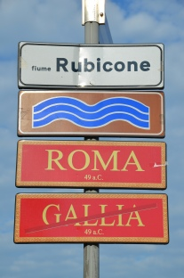 Street signs marking the limit of Julius Caesar's province, Roman bridge over the Rubicon river, Savignano sul Rubicone, Italy. Image © Carole Raddato.
