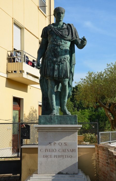 Modern statue of Julius Caesar next to the Roman bridge over the Rubicon river on the Via Aemilia, Savignano sul Rubicone, Italy