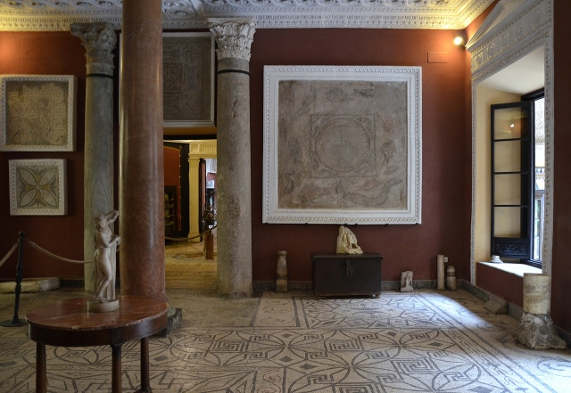 The Columns room, paved with a geometric mosaic and decorated with fragments of mosaics on the walls and two Roman colums, one made of green marble and the other made of a mixture of various colors. Baetica route mosaics.