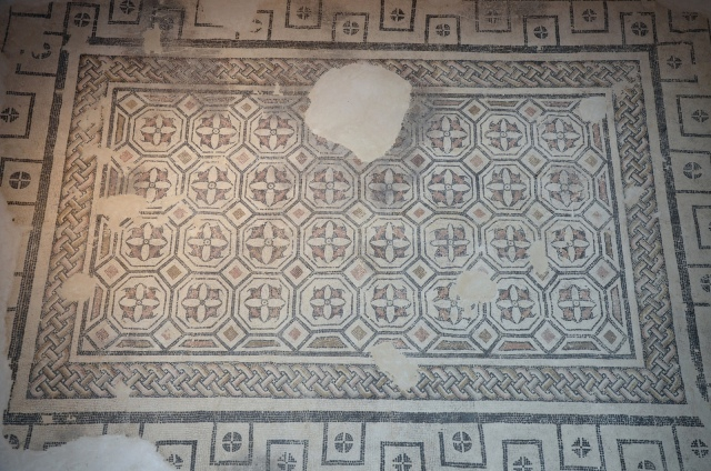 Geometric mosaic with octagons framed by a meander border, it shows deterioration by fire, Roman Mosaic Museum, Casariche