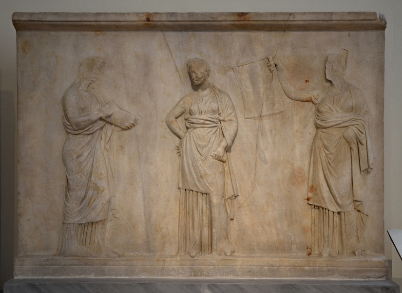 Relief slab from a pedestal, three Muses holding musical instruments and scrolls, found in Mantineia, it formed the revetment of a pedestal for the statues of the Delian trinity (Leto, Apollo & Artemis), c. 340 BC, National Archaeological Museum of Athens