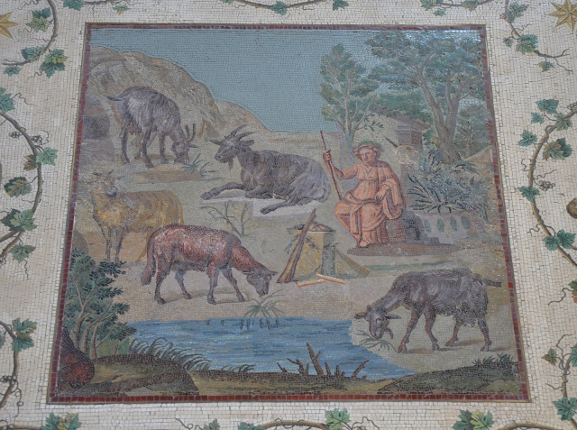 Mosaic panel depicting a rocky landscape with goats by a stream and a seated statue of Dionysus.