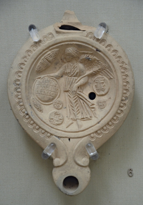 Terracotta oil lamp, on the discus a winged Victory holds a shield on which is inscribed Happy New Year, surrounded by New Year's gifts, made in Italy, around 50-100 AD, British Museum